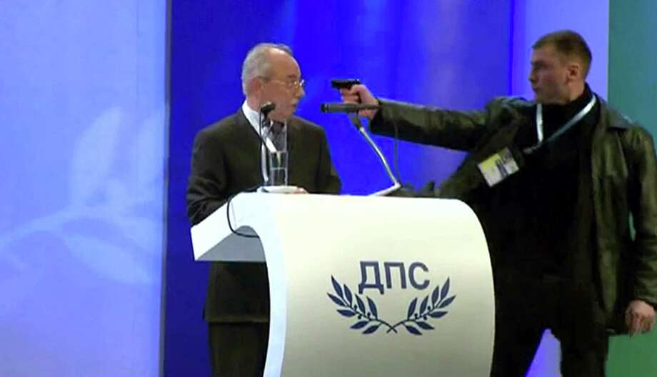 Image grab from video shows a man identified as Oktai Enimehmedov, 25, as he points a weapon at Ahmed Dogan, left, leader of the Movement for Rights and Freedoms, during his speech at his party's congress in Sofia, on Saturday Jan. 19, 2013. Dogan struck the man before other delegates wrestled the assailant to the ground, and no shots were fired.  Police took the man away.(AP Photo/ BTVnews) Photo: Btv News
