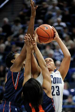 Connecticut's Kaleena Mosqueda-Lewis, right, is guarded by Syracuse's Kayla Alexander, left, and Cornelia Foundren during the first half of an NCAA college basketball game in Hartford, Conn., Saturday, Jan. 19, 2013. (AP Photo/Fred Beckham) Photo: Fred Beckham, Associated Press / FR153656 AP