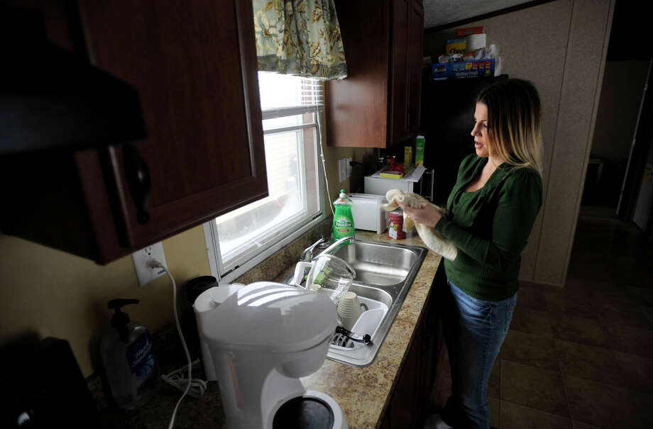 Hurricane Sandy evacuee Kelly Ackermann, of Staten Island, N.Y., finishes washing dishes in the sink of a mobile home that was provided to her family by Faith Church in New Milford. Photographed on Wednesday, Jan. 16, 2013. Kelly and her husband, Scott, moved in last Friday. This is the Ackermann's fourth move since the hurricane hit. They both are currently looking for work locally so they can stay. Photo: Jason Rearick / The News-Times