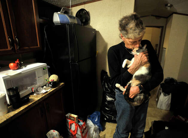 "Staten Island evacuee Maryann Daino kisses her cat, Edie, inside a mobile home trailer that was provided by Faith Church in New Milford. Photographed on Wednesday, Jan. 16, 2013. Daino moved in the day before. The mobile home next to the church parking lot is Daino's fourth temporary housing unit since Hurricane Sandy made her Staten Island home uninhabitable. After she said she saw a 60-foot wave her ""whole neighborhood was like a river."" Photo: Jason Rearick / The News-Times"