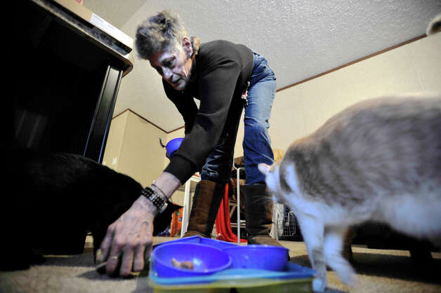 Staten Island evacuee Maryann Daino feeds her cats inside a mobile home trailer that was provided by Faith Church in New Milford. Photographed on Wednesday, Jan. 16, 2013. Photo: Jason Rearick / The News-Times