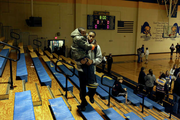 "William Gates carries his brother, Marques Gates, 9, after his basketball game at Samuel Clemens High School against Kerrville Tivy on Tuesday, Jan. 15, 2013. Their father, William Gates Sr., was the one of two high school basketball players featured in the documentary ""Hoop Dreams."" Photo: Lisa Krantz, Express-News / © 2012 San Antonio Express-News"