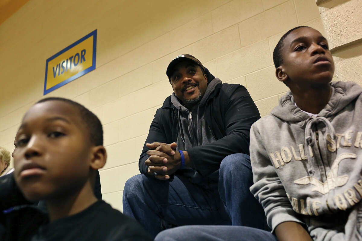 William Gates, who was the one of two high school basketball players featured in the documentary, Hoop Dreams, watches his son's basketball game with his other sons, Marques, 9, left, and Jalon, 14, right, at Samuel Clemens High School against Kerrville Tivy in Schertz on Tuesday, Jan. 15, 2013.