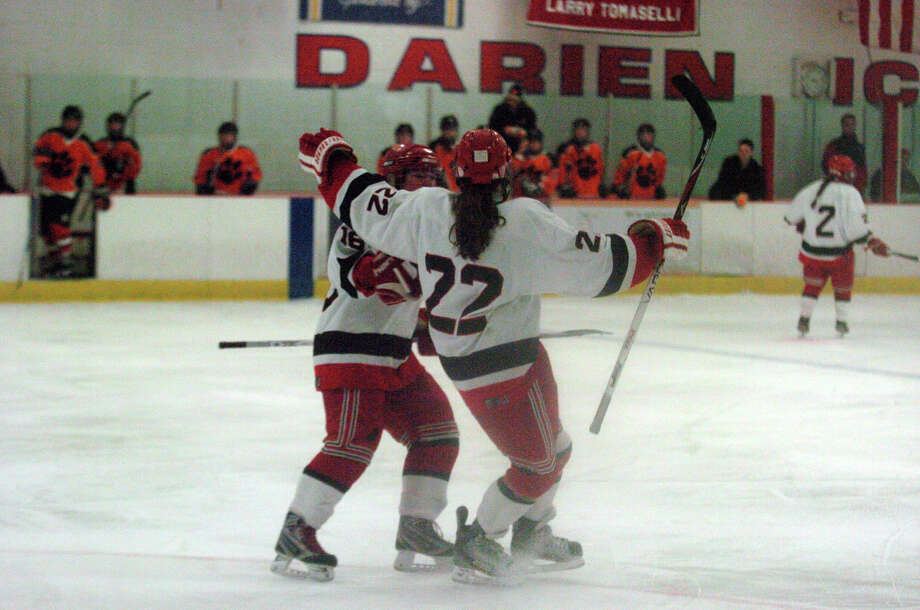 New Canaan's Olivia Hompe celebrates her goal with a hug from teammate Corbett Ripley, left, as New Canaan hosts Ridgefield High School in a girls hockey game at the Darien Ice Rink in Darien, Conn., Jan. 19, 2013. Photo: Keelin Daly / Stamford Advocate Riverbend Stamford, CT