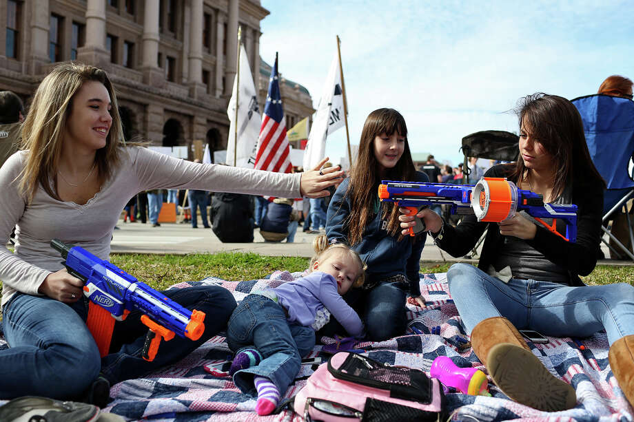Hannah O'Neal, 13 (from left); Liberty O'Neal, 2; Nyah Anglin, 10; and Moriah O'Neal, 15, entertain themselves with toy guns during the state Capitol rally organized by the group Guns Across America. Photo: Lisa Krantz, San Antonio Express-News / © 2012 San Antonio Express-News