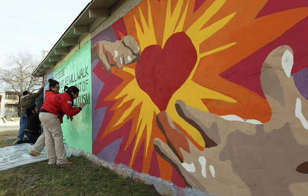 City Year's Christina Flores (foreground) and Sarah Beverly join other volunteers in touching up a mural that was done in honor of civil rights leader Martin Luther King Jr. Photo: Kin Man Hui, San Antonio Express-News / © 2012 San Antonio Express-News