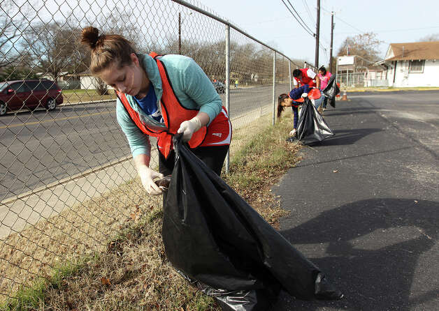 Ashlyn Duran, a student at Our Lady of the Lake University, and other volunteers pick up debris along Martin Luther King Boulevard in preparation for Monday. Photo: Kin Man Hui, San Antonio Express-News / © 2012 San Antonio Express-News