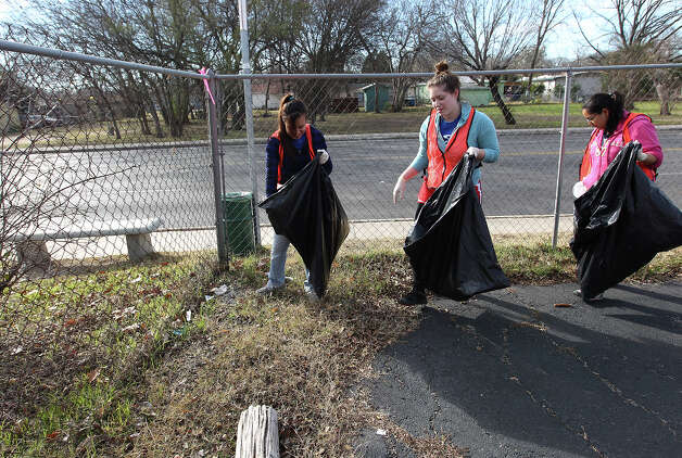 "Chloe Wolfe (from left), Ashlyn Duran and Grace Chavez, all from Our Lady of the Lake University, volunteer in a clean-up effort along Martin Luther King Boulevard on Saturday, Jan. 19, 2013. Volunteers along with City Year joined the MLK Commission's ""Day of Service"" with a clean-up effort, landscaping and community revitalization. The MLK March will take place on Monday. Photo: Kin Man Hui, San Antonio Express-News / © 2012 San Antonio Express-News"
