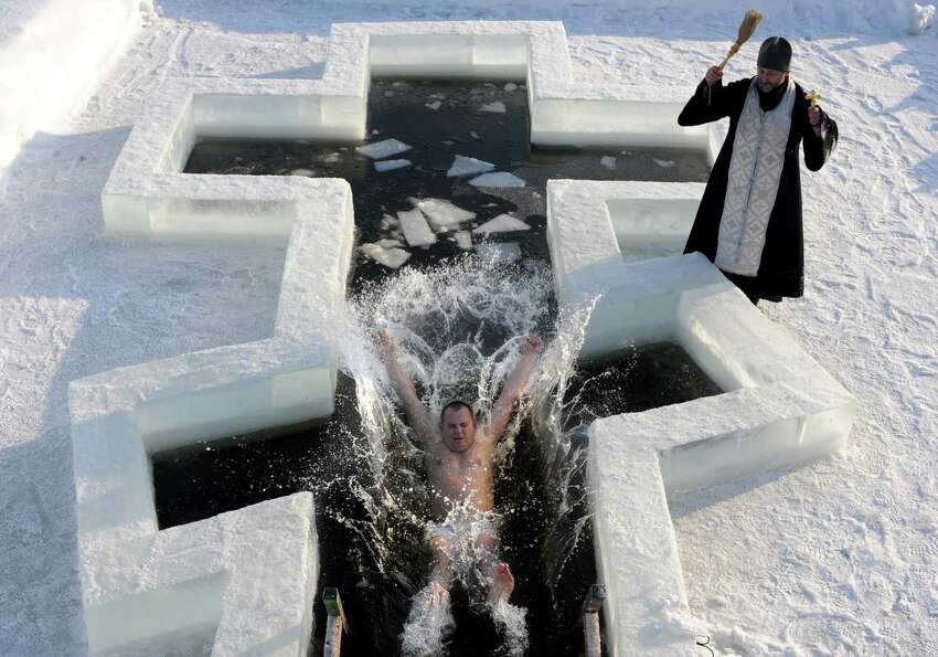 A Belarus Orthodox believer plunges into icy waters as a priest blesses him on the eve of the Epipha