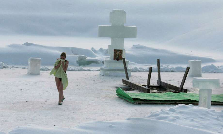 A woman walks away after taking a bath in ice cold water,  in an ice hole of the pond,  in the Kolomenskoye park on the outskirts of Moscow, Russia, Saturday, Jan. 19, 2013. Photo: Mikhail Metzel, Associated Press / AP