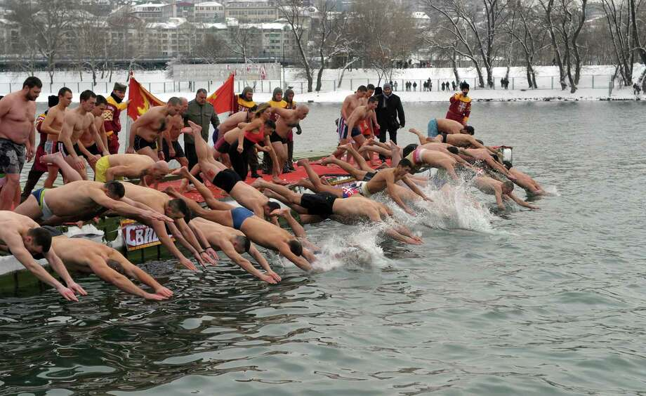 Serbian swimmers jump in the cold waters of the Sava lake as they compete to reach a cross in Belgrade on Epiphany Day on January 19, 2013. It is believed that the man who grabs the cross first, thrown into the water by an Eastern Orthodox priest, will be healthy throughout the New Year. Photo: ALEXA STANKOVIC, AFP/Getty Images / AFP
