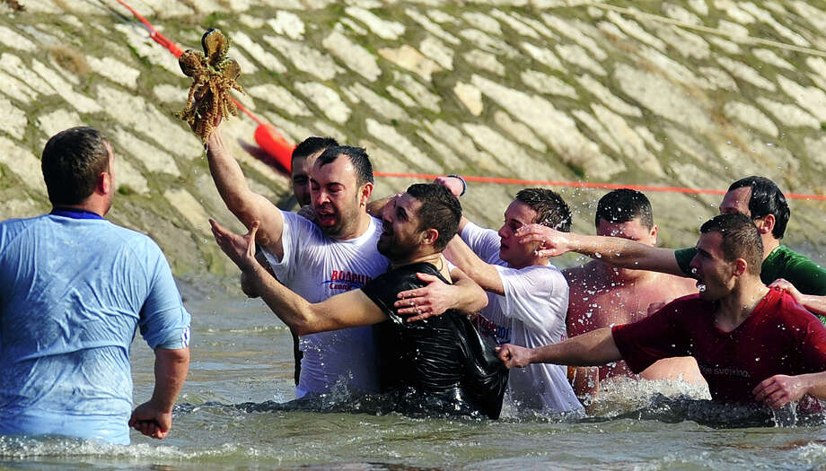 Christian Orthodox Dejan Arsovski, 35, retrieves a wooden cross from the Vardar River during an Epiphany ceremony to bless the waters in Skopje, Macedonia, on Saturday, Jan. 19, 2013. Photo: BORIS GRDANOSKI, Associated Press / AP