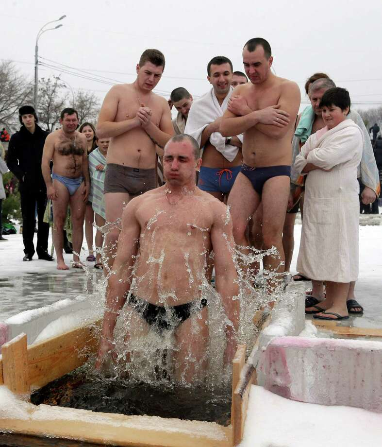 A man jumps into an ice hole in the Dnipro River, as others wait for their turn, as part of celebration of the Epiphany in the town of Vyshgorod outside the capital Kiev, Ukraine, Saturday, Jan. 19, 2013. Orthodox believers celebrate the holiday of the Epiphany on Jan. 19, and traditionally bathe in holes cut through thick ice on rivers and ponds to cleanse themselves with water deemed holy for the day. Photo: Efrem Lukatsky, Associated Press / AP