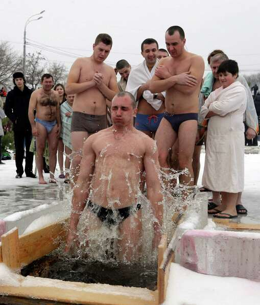A man jumps into an ice hole in the Dnipro River, as others wait for their turn, as part of celebrat