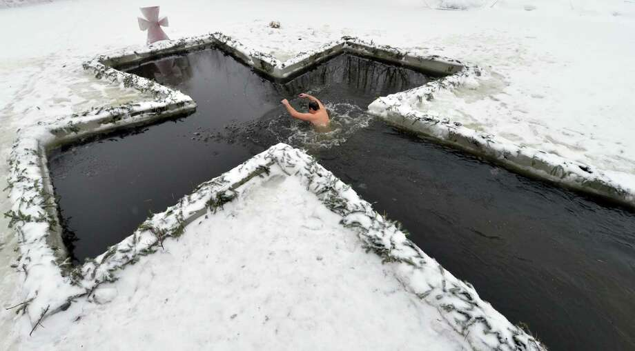 A man plunges into an ice-hole during celebration of Orthodox Epiphany in  Kiev on January 19, 2013. Photo: SERGEI SUPINSKY, AFP/Getty Images / AFP