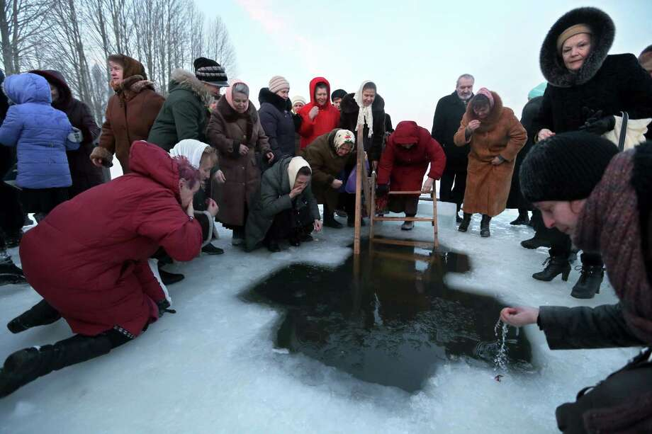 Orthodox believers wash faces with water from the hole after the consecration by its priest to mark Epiphany in Minsk, Belarus, Saturday, Jan. 19, 2013. Thousands of Russian Orthodox Church followers plunged into icy rivers and ponds across the country to mark Epiphany, during which they cleanse themselves with water deemed holy for the day. Water that is blessed by a cleric on Epiphany is considered holy and pure until next year's celebration, and is believed to have special powers of protection and healing. Photo: Sergei Grits, Associated Press / AP