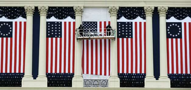 Two workers adjust US flags on the US Capitol as preparations continue for the second inauguration of US President Barack Obama in Washington, DC, on January 17, 2013. Obama faces a near impossible task in his second inaugural address on January 21: uniting a nation in which the compromise that oils governing is crushed by deep political divides. Before a crowd of thousands and the eyes of the world on television and online, Obama will stand on the West Front of the US Capitol and swear to faithfully execute the office of president and defend the Constitution. Photo: JEWEL SAMAD, AFP/Getty Images / AFP