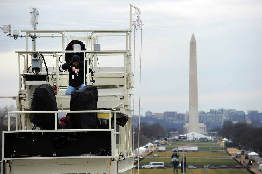 Agence France-Presse technician Richardo Criales (L) works on a tower on the US Capitol erected for media coverage for the second inauguration of US President Barack Obama in Washington, DC, on January 17, 2013. Obama faces a near impossible task in his second inaugural address on January 21, uniting a nation in which the compromise that oils governing is crushed by deep political divides. Before a crowd of thousands and the eyes of the world on television and online, Obama will stand on the West Front of the US Capitol and swear to faithfully execute the office of president and defend the Constitution. Photo: JEWEL SAMAD, AFP/Getty Images / AFP