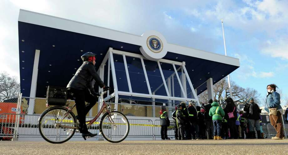 "A cyclist prepares to pass visitors standing in front of the Inaugural Parade Reviewing Stand outside the White House on Pennsylvania Avenue in Washington, Friday, Jan. 18, 2013, in preparation for this weekend's 57th Presidential Inauguration"" where President Barack Obama will be sworn in for a second term. Photo: Susan Walsh, Associated Press / AP"