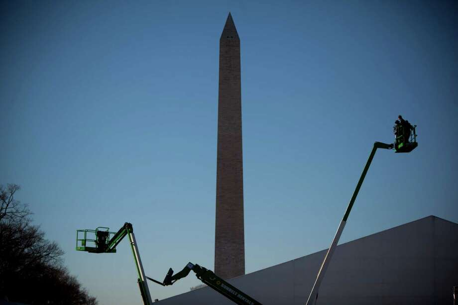 A set of cranes assist in adding the finishing touches to a tent set up for inaugural events on the National Mall January 19, 2013 in Washington DC.  The U.S. capital is preparing for the second inauguration of U.S. President Barack Obama, which will take place on January 21. Photo: Allison Shelley, Getty Images / 2013 Getty Images