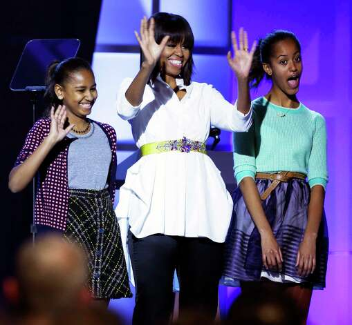 "First lady Michelle Obama, center, and daughters Sasha, left, and Malia, right, react during the Kids' Inaugural: Our Children. Our Future."" event in Washington, Saturday, Jan. 19, 2013, as part of the 57th Inauguration weekend of events. Photo: Frank Franklin II, Associated Press / AP"