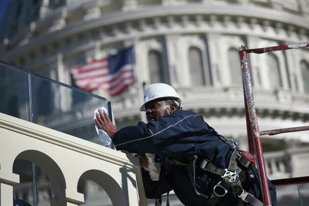 A worker cleans bulletproof glass on the west Capitol platform where President Barack Obama will take the oath of office during his second inauguration on January 19, 2013 in Washington, D.C. Preparations continued ahead of Monday's event, which is expected to draw more than half a million people. Photo: John Moore, Getty Images / 2013 Getty Images