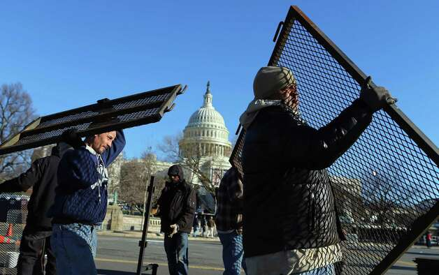 Workers place security fences in place near the Capitol building as the area is prepared for the Presidential inauguration on January 19, 2013 in Washington, DC.  The US capital is preparing for the second inauguration of US President Barack Obama, which will take place on January 21. Photo: Joe Raedle, Getty Images / 2013 Getty Images