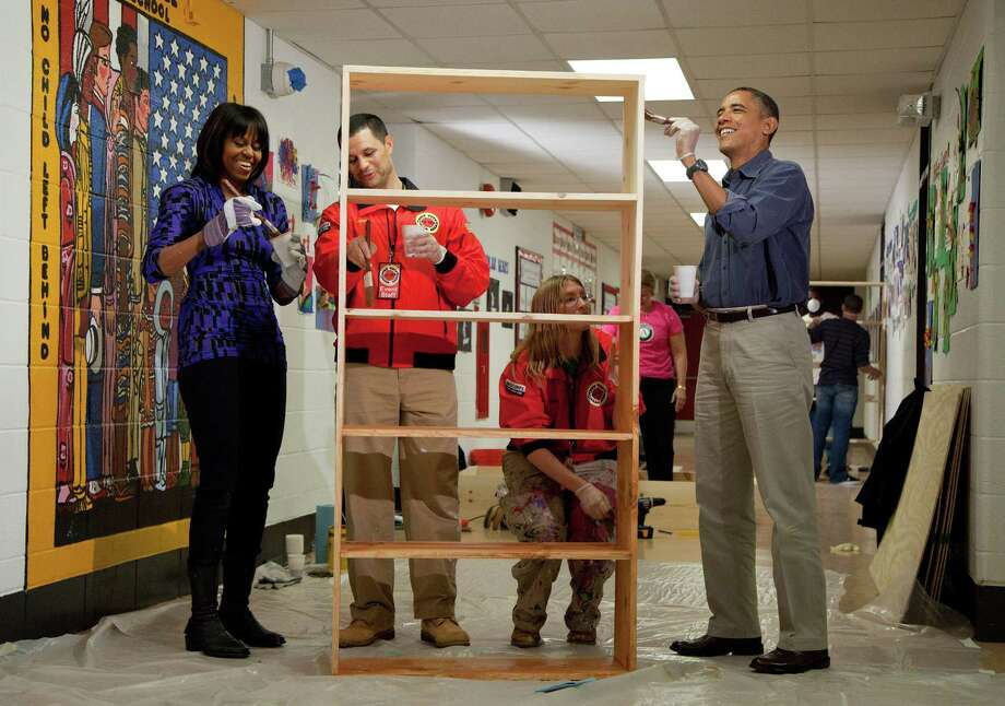 President Barack Obama and first lady Michelle Obama help to stain a bookshelf at Burrville Elementary School in Washington, D.C., Saturday, January 19, 2013. Joining the Obamas are Jeff Franco, Executive Director of City Year, and Sheri Fisher, a City Year employee. The event was part of the National Day of Service, the first official event of the 57th presidential inauguration weekend. Photo: Martin H. Simon, McClatchy-Tribune News Service / Corbis