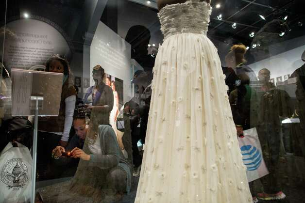 "Visitors crowd around a display featuring the dress worn by Michelle Obama on inauguration day 2009 at an exhibition entitled ""The First Ladies"" at the National Museum of American History January 19, 2013 in Washington DC.  The U.S. capital is preparing for the second inauguration of U.S. President Barack Obama, which will take place on January 21. Photo: Allison Shelley, Getty Images / 2013 Getty Images"