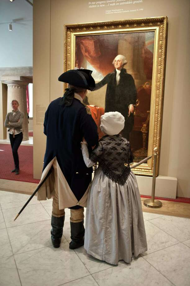 Actors dressed as George Washington and his wife Martha look at a portrait of the first US president by Gilbert Stuart at the National Portrait Gallery in Washington on January 19, 2013, two days before the second inauguration of the 44th President, Barack Obama. Photo: NICHOLAS KAMM, AFP/Getty Images / AFP