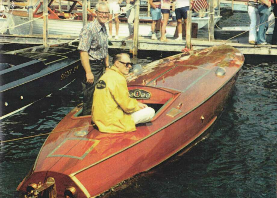 Bill Morgan (standing) in one of his wooden racing boats in this undated photograph.