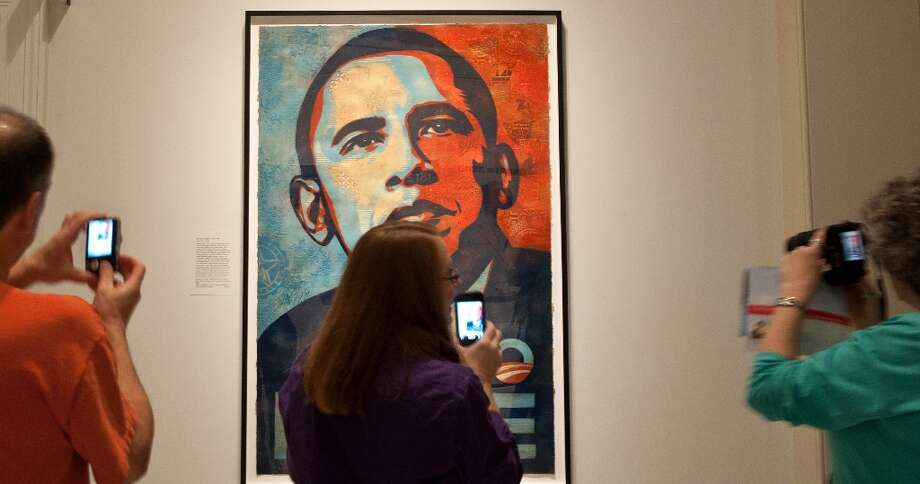 Visitors take pictures of Shepard Fairey's portrait of US President Barack Obama, based on a photograph by Mannie Garcia, at the National Portrait Gallery in Washington on January 19, 2013, two days before Obama's second inauguration. Photo: NICHOLAS KAMM, AFP/Getty Images / AFP