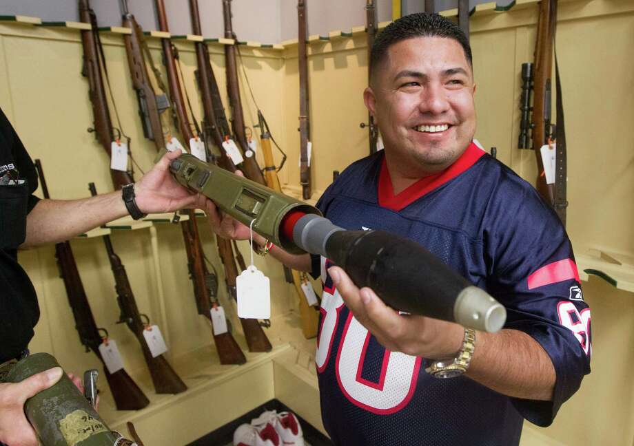 "Saul Silva puts a replica shell into his new ""conversation piece,"" an M72A3 antitank rocket-launcher, at Saturday's auction of the personal collection of the late Bill James, founder of the Arms Room in League City. Photo: J. Patric Schneider, Freelance / © 2013 Houston Chronicle"