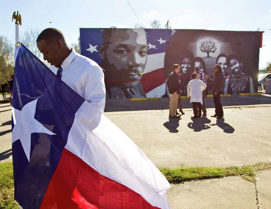 Chase Washington, of DR Financial Services, put up a Texas flag for the unveiling ceremony for a new mural featuring Dr. Martin Luther King and the Obama family. The mural was done by Reginald Adams John Foreman and Acie Washington. Photo: Nick De La Torre, Staff / © 2013  Houston Chronicle