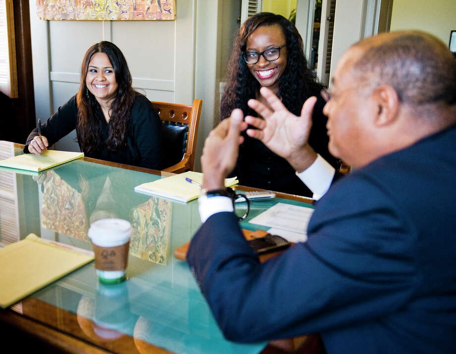 Interns Mili Gosar, 24, left, of Houston, and Adenike Adesokan, 25, center, of Chicago, IL react to a comment by Texas Sen. Rodney Ellis, right, during a meeting with six of his interns inside Ellis' office at the Texas state capitol in Austin, TX on Wed., Jan 16, 2013. Ashley Landis for the Houston Chronicle Photo: Ashley Landis, For The Houston Chronicle / copyright 2013 Ashley Landis
