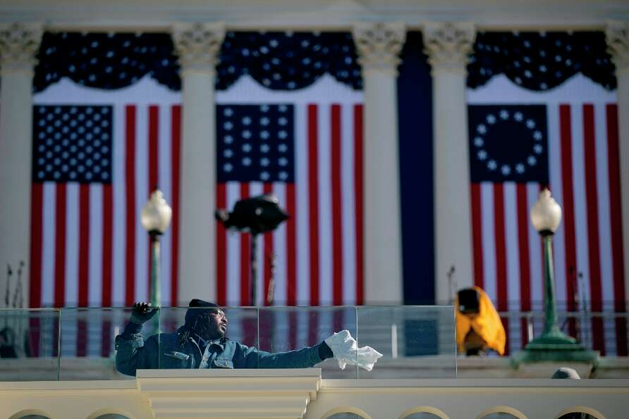 A worker cleans the bulletproof glass that surrounds the inaugural platform outside the U.S. Capitol