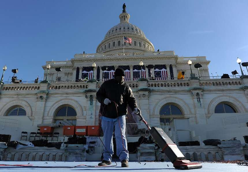 A worker vacuums a platform at the US Capitol as preparations continue for the second inauguration o