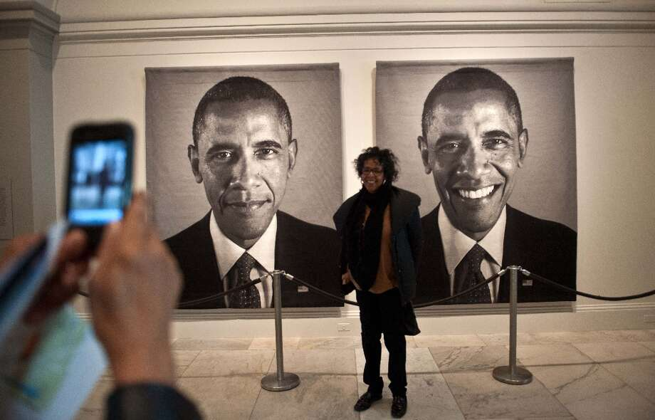 A woman has her picture taken in front of a diptych of US President Barack Obama by Chuck Close at the National Portrait Gallery in Washington on January 19, 2013, two days before Obama's second inauguration. Photo: NICHOLAS KAMM, AFP/Getty Images / AFP