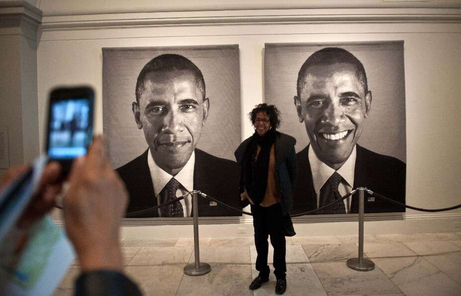 A woman has her picture taken in front of a diptych of US President Barack Obama by Chuck Close at t
