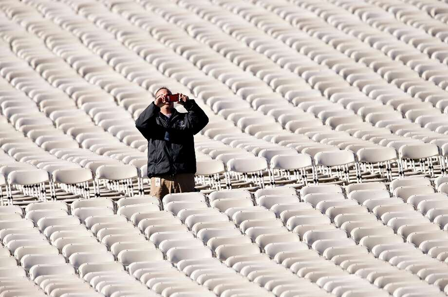 Two days before President Obama's second inauguration, a workman snaps a souvenir photo amid thousands of folding chairs on the West Lawn on Capitol Hill in Washington, Saturday, Jan. 19, 2013, where thousands of folding chairs await the festivities for the 57th Presidential Inauguration and the start of President Barack Obama's second term. Photo: J. Scott Applewhite, Associated Press / AP