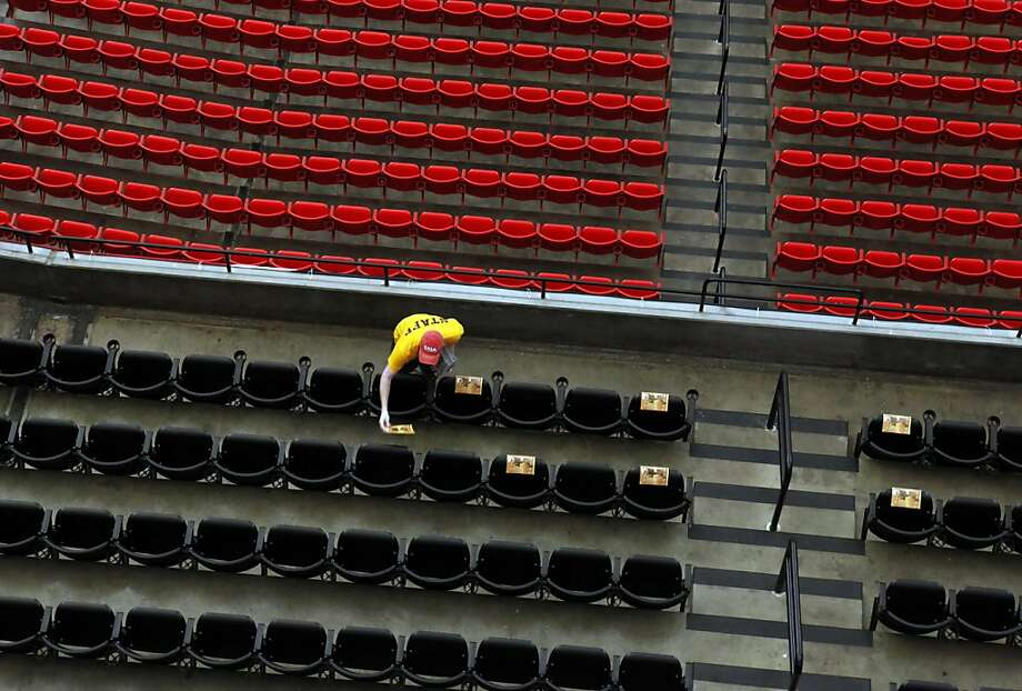 A worker places programs on seats at the Georgia Dome amid preparations for the NFC Championship Game in Atlanta. Photo: Carlos Avila Gonzalez, The Chronicle