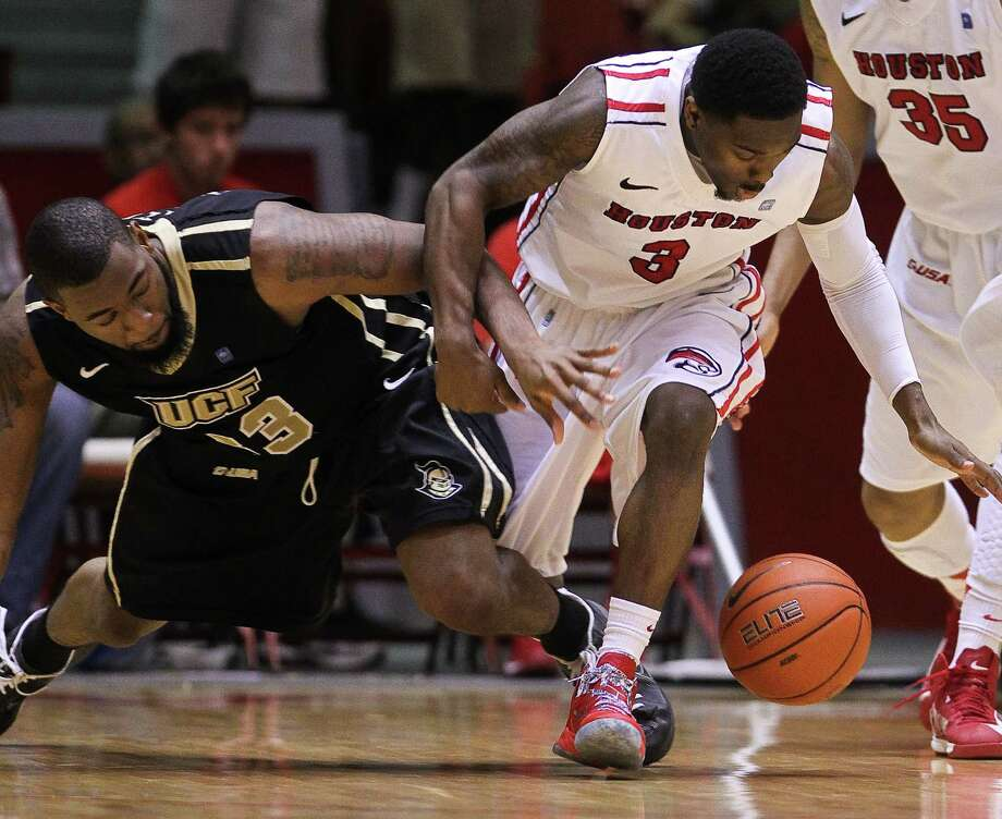 Houston Guard J.J. Thompson, right, steals the bal from Central Florida forward Keith Clanton to keep the Cougars in the game during the second half of an NCAA basketball game, Saturday, Jan. 19, in Hofheinz Pavilion in Houston. Photo: Nick De La Torre, Houston Chronicle / © 2013  Houston Chronicle