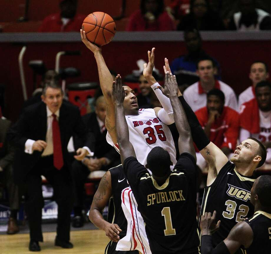 Houston forward TaShawn Thomas, center, rises above a host of Central Florida defenders to get of his baby hook shot during the second half of an NCAA basketball game, Saturday, Jan. 19, in Hofheinz Pavilion in Houston. Photo: Nick De La Torre, Houston Chronicle / © 2013  Houston Chronicle