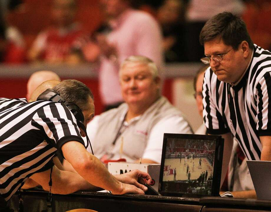Officials look at the video of a last-second shot by Central Florida during the second half. The shot was ruled no good and the game went on to overtime. Photo: Nick De La Torre, Houston Chronicle / © 2013  Houston Chronicle