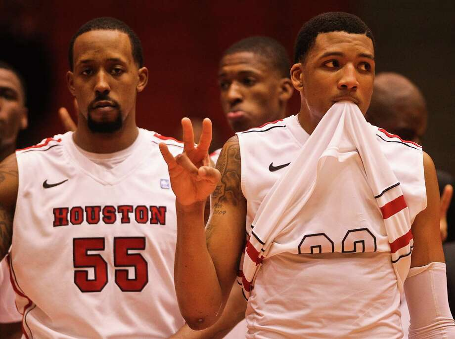 Houston Forwards J.J. Richardson, eft, and TaShawn Thomas watch the central Florida players celebrate with their fans after loosing to them after a NCAA basketball game, Saturday, Jan. 19, in Hofheinz Pavilion in Houston. Photo: Nick De La Torre, Houston Chronicle / © 2013  Houston Chronicle