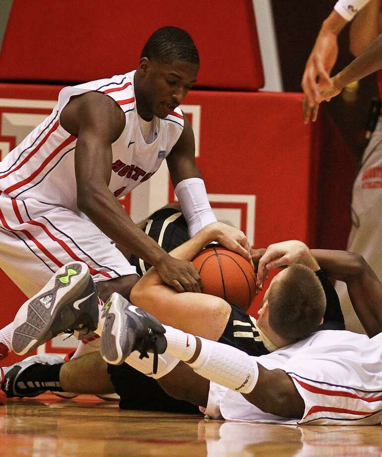 Houston forward Mikhail McLean fight with Central Florida forward Kasey Wilson for a loose ball during the first half of an NCAA basketball game, Saturday, Jan. 19, in Hofheinz Pavilion in Houston. Photo: Nick De La Torre, Houston Chronicle / © 2013  Houston Chronicle