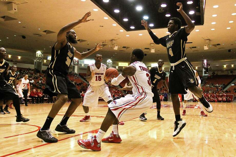 Houston guard J.J. Thompson (3), works hard to get the ball to forward Leon Gibson as the Central Florida defense collapses around him during the second half of an NCAA basketball game, Saturday, Jan. 19, in Hofheinz Pavilion in Houston. Photo: Nick De La Torre, Houston Chronicle / © 2013  Houston Chronicle