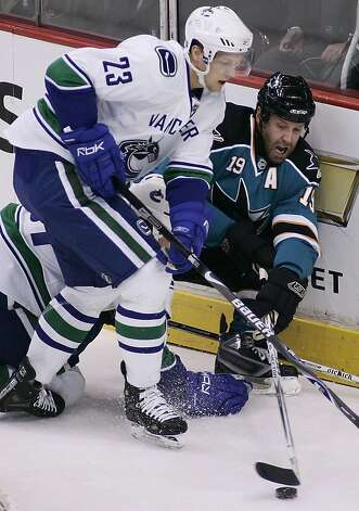 File-This Oct. 15, 2007 file photo shows San Jose Sharks' Joe Thornton (19) trying to play the puck while getting checked into the end boards by Vancouver Canucks' Alex Edler (23), of Sweden, during the first period of NHL hockey action in Vancouver.  The  Canucks re-signed Edler to a six-year deal on Friday Jan. 18, 2013. The 26-year-old had 11 goals and 38 assists in 82 games with the Canucks last season. (AP Photo/Richard Lam, The Canadian Press,File) Photo: Richard Lam, Associated Press