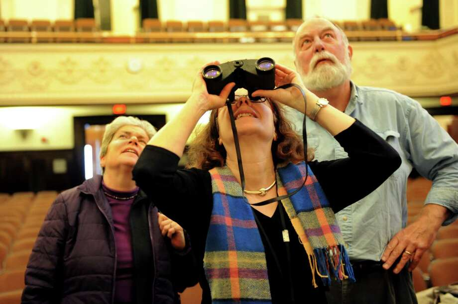 "Shelly Drazen of Albany, center, uses binoculars to view details of Adolphe Yvon's 1870 mural ""The Genius of America"" in Chancellors Hall auditorium on Wednesday, Jan. 16, 2013, at the State Education Building in Albany, N.Y. Joining Drazen are Karen Kaufmann of Schodack, left, and George Webb, former director of Facilities at the State Education Building. The mural has been hidden behind a curtain for more than a decade. (Cindy Schultz / Times Union) Photo: Cindy Schultz / 00020804A"