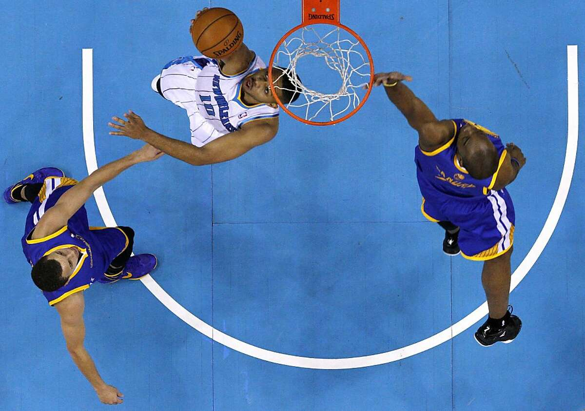 New Orleans Hornets guard Eric Gordon, center, shoots the ball as Golden State Warriors forward Carl Landry, right, and guard Stephen Curry, left, defend during the first half of an NBA basketball game in New Orleans, Saturday, Jan. 19, 2013. (AP Photo/Jonathan Bachman)